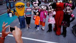 Seorang pengunjung berfoto bersama sejumlah karakter kartun di Times Square, New York, Selasa (21/6). Kehadiran karakter-karakter kartun tersebut mengundang warga untuk foto bersama. (REUTERS/Lucas Jackson)