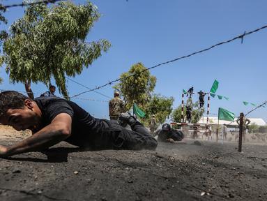 Sejumlah kadet Palestina melewati rintangan kawat berduri saat berlatih fisik dengan militer Hamas, Brigade Ezzedin al-Qassam, di Kota Gaza (20/7/2019). Sejumlah pemuda Palestina direkrut Hamas untuk menjadi bagian anggotanya. (AFP Photo/Mahmud Hams)
