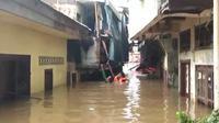 Seorang Warga Berenang Untuk Membagikan Makanan Bagi Korban Banjir di Kebon Pala, Jakarta Timur, Rabu (1/1/2020). (Foto: Nanda Perdana Putra/Liputan6.com)