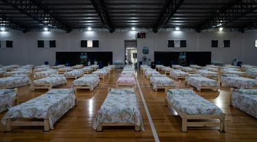 Tempat tidur untuk pasien terinfeksi virus corona Covid-19 diletakkan di gimnasium tempat berlatih timnas futsal Asosiasi Sepakbola Argentina (AFA) di pinggiran Buenos Aires, Senin (13/4/2020). Sekitar 120 tempat tidur tersedia di markas timnas futsal AFA untuk merawat pasien. (AP/Victor R. Caivano)