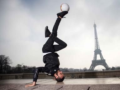 Moss dari S3 Society dance group beraksi bersama bola di the Place du Trocadero, dengan  latar menara Effeil, Paris, Jumat (18/3/2016).  S3 Society akan tampil pada Euro 2016 Pracis tanggal 10 Juni-10 Juli 2016. (AFP/Lionel Bonaventure)