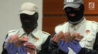 Penyidik KPK menunjukkan barang bukti uang hasil Operasi Tangkap Tangan (OTT) Bandung Barat di Gedung KPK, Jakarta, Rabu (11/4). KPK menyita uang sebesar Rp 435 juta. (Merdeka.com/Dwi Narwoko)