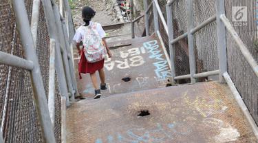 Seorang anak menuruni tangga di JPO di kawasan Tebet, Jakarta, Selasa (6/3). Kondisi JPO yang memprihatinkan menyebabkan sebagian warga lebih memilih untuk tidak menggunakannya karena membahayakan keselamatan. (Liputan6.com/Immanuel Antonius)