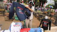 Pedagang menjual kaos #2019GantiPresiden di halaman Masjid Istiqlal, Jakarta, Jumat (10/8). Kaos dijual dengan harga Rp 50-55 ribu per buah untuk lenga pendek dan lengan panjang. (Liputan6.com/Fery Pradolo)