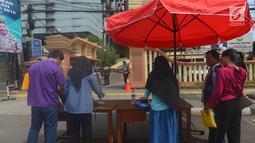 Warga menaruh barang bawaannya sebelum memasuki Polres Jakarta Timur, Rabu (16/5). Sebelumnya telah terjadi serangan dari orang tak dikenal di Mapolda Riau yang menewaskan satu orang polisi pada Rabu (16/5/18) pagi. (Merdeka.com/Imam Buhori)