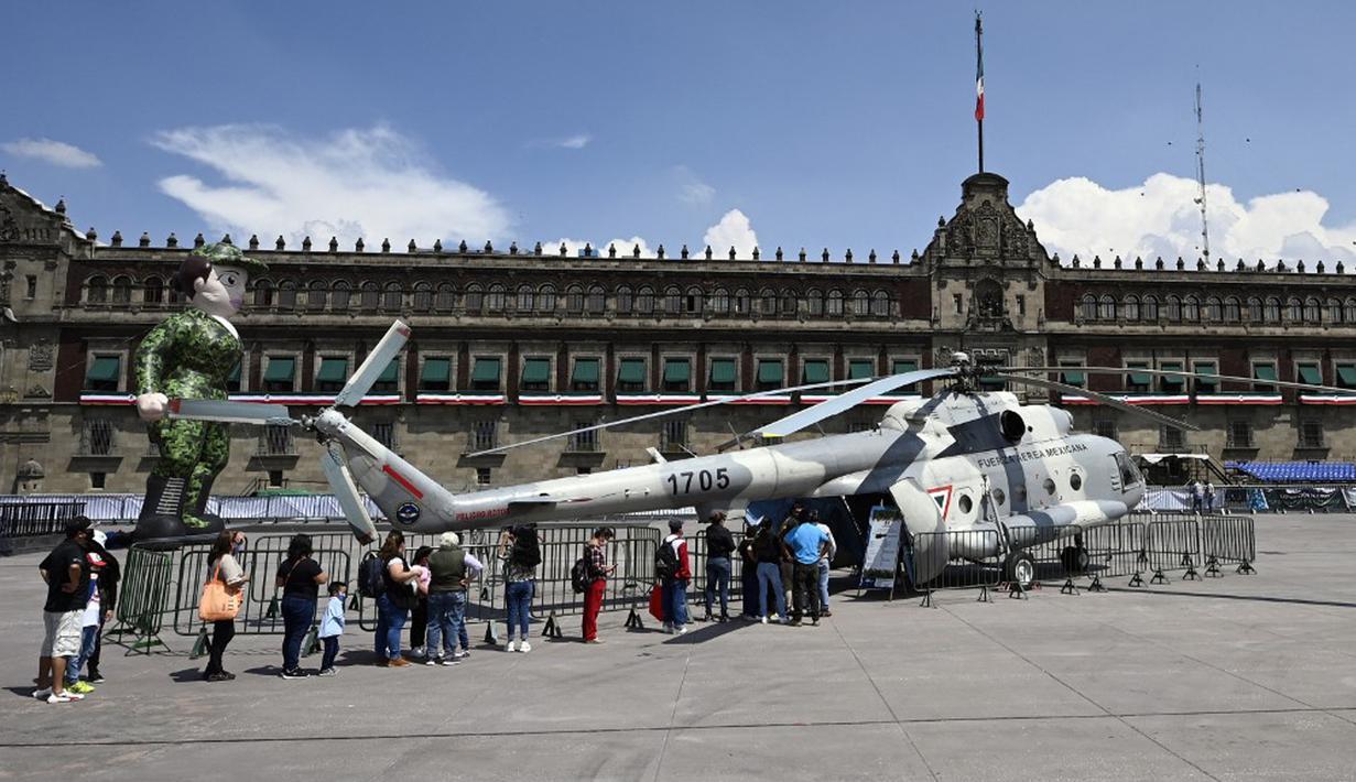 Orang-orang mengantre untuk masuk ke helikopter MI-17 Angkatan Udara Meksiko dalam pameran yang disebut The Great Force of Mexico di Alun-Alun Zocalo, Mexico City, Meksiko, 20 September 2021. (ALFREDO ESTRELLA/AFP)