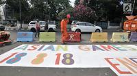 Pekerja dari PPSU Kelurahan Pegangsaan saat menyelesaikan pembuatan maskot dan logo Asian Games 2018 di Jalan Penataran atau Simpang Tugu Proklamasi, Jakarta, Rabu (25/7).  (Merdeka.com/Iqbal S. Nugroho)