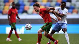 Striker Portugal, Diogo Jota (kiri) menguasai bola dibayangi gelandang Israel, Gadi Kinda dalam laga uji coba menjelang Euro 2020 di Jose Alvalade Stadium, Lisbon, Rabu (9/6/2021). Portugal menang 4-0 atas Israel. (AFP/Patricia De Melo Moreira)