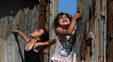 Anak-anak bermain di rumah mereka saat Hari Nakba di kamp pengungsian Al-Shati, Jalur Gaza, Palestina, Rabu (15/5/2019). Rakyat Palestina memperingati 71 tahun Hari Nakba yang berarti 'malapetaka'. (MOHAMMED ABED/AFP)