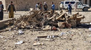 Personel keamanan dan penduduk berkumpul di sekitar lokasi bom mobil yang menargetkan markas besar polisi Afghanistan di Feroz Koh, ibu kota Ghor.