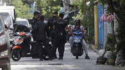 Polisi berbicara dengan seorang warga di sebuah desa yang dikunci karena jumlah kasus COVID-19 di antara warga di Manila, Filipina (11/3/2021). Polisi juga tidak mengizinkan kedua hotel itu selama tiga hari penguncian dan pelanggar akan dipaksa menjalani karantina 14 hari. (AP Photo/Aaron Favila)
