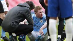 Gelandang Manchester City, Kevin De Bruyne mendapat perawatan dari tim medis usai mengalami cedera saat menghadapi Chelsea dalam laga semifinal Piala FA 2020/2021 di Wembley Stadium, London, Sabtu (17/4/2021). Manchester City kalah 0-1 dari Chelsea. (AFP/Ian Walton/Pool)
