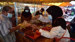 Orang-orang memakai masker di kios-kios yang dikelilingi oleh pelindung plastik di pasar, sebagai bagian dari upaya untuk menghentikan penyebaran virus corona Covid-19, selama bulan suci Ramadhan di provinsi selatan Thailand, Narathiwat (17/4/2021). (AFP/Madaree Tohlala)