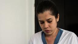 Petugas medis, Leidy Garcia menyiapkan potongan pita dengan koordinat Braille untuk pemeriksaan payudara di sebuah rumah sakit di Cali, Kolombia (14/11). Leidy Garcia dan Francia Papamija bekerja sebagai Medical Tactile Examiners. (AFP/Luis Robayo)