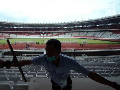 Pekerja membersihkan kaca tribun VIP di Stadion Gelora Bung Karno, Jakarta, Jumat (12/1). Rencananya, Stadion GBK akan diresmikan penggunaannya pasca renovasi oleh Presiden Joko Widodo, Minggu (14/1). (Liputan6.com/Helmi Fithriansyah)