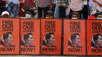 Pengunjuk rasa antikudeta duduk di belakang poster dengan gambar pemimpin Myanmar yang digulingkan Aung San Suu Kyi selama unjuk rasa di Yangon, Myanmar, Senin (22/2/2021). Meski ada peringatan dari militer Myanmar, peserta demonstrasi tidak gentar. (AP Photo)