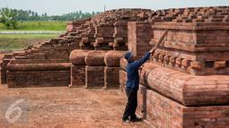 Pekerja melakukan perawatan rutin Candi Blandongan, Batujaya, Kerawang, Jawa Barat (9/5).Perawatan candi meliputi pembersihan lumut, jamur dan rumput yang tumbuh di permukaan batu untuk menghindari pelapukan. (Liputan6.com/Gempur M Surya)