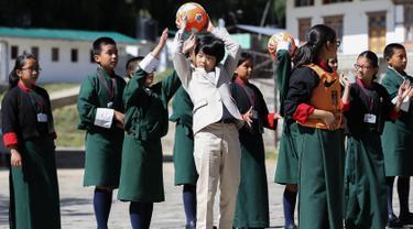 Pangeran Hisahito (tengah) berusia 12 tahun dari Jepang mengoper bola saat bermain bersama siswa setempat saat mengunjungi sebuah sekolah di Thimpu, Bhutan, Selasa (20/8/2019). (AFP Photo/Japan Out/Jiji Press)