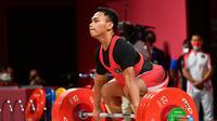 Lifter Indonesia Eko Yuli Irawan saat berlaga dalam cabang angkat besi 61kg putra pada Olimpiade Tokyo 2020 di Tokyo International Forum, Jepang, Minggu 25 Juli 2021. (Vincenzo PINTO / AFP)