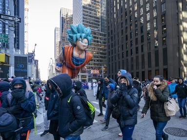Balon Goku melayang di atas kawasan Sixth Avenue selama Parade Macy's Thanksgiving Day di New York, Kamis (22/11). Balon raksasa berbentuk ikon-ikon kartun terkenal menghiasi gelaran yang digelar untuk ke-92 tersebut. (Don EMMERT / AFP)