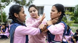 Juara karate internasional Muslim India, Syeda Falak mengajari teknik bela diri kepada dua siswi di Telangana Minorities Residential Girls School di Hyderabad, India (17/6). (AFP Photo/Noah Seelam)