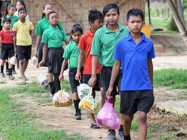 Gambar pada 20 Mei 2019, siswa India mengantre membawa tas plastik berisi sampah plastik di sekolah Forum Akshar di desa Pamohi, Guwahati. Sekolah ini mengambil pendekatan baru untuk mengatasi momok sampah plastik dengan menjadikannya sebagai syarat pengganti biaya sekolah. (Biju BORO/AFP)