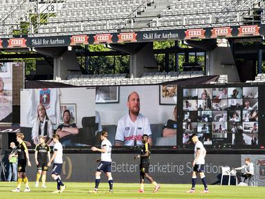 Penonton menyaksikan pertandingan Liga Denmark antara AGF dengan Randers FC melalui aplikasi video conference di Ceres Park, Aarhus, Denmark, Kamis (28/5/2020). Laga ini menjadi pertandingan pertama yang melibatkan suporter melalui aplikasi pertemuan virtual. (Henning Bagger/Ritzau Scanpix via AP)