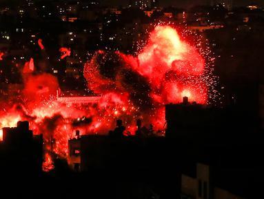 Bola api meledak di atas kantor stasiun televisi Al Aqsa milik Hamas selama serangan udara Israel di Jalur Gaza, Senin (12/11). Serentetan tembakan roket Israel di Gaza menewaskan tiga orang Palestina dan menghancurkan gedung TV Hamas. (Mahmud Hams/AFP)