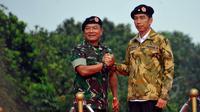Presiden Joko Widodo dan Panglima TNI Jenderal Moeldoko  saat mengikuti upacara pengangkatan Presiden Jokowi sebagai warga kehormatan Pasukan khusus TNI di Markas Besar TNI Cilangkap, Jakarta Timur, Kamis (16/4/2015). (Liputan6.com/Yoppy Renato)