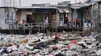 Warga beraktivitas di antara sampah yang mengelilingi Kampung Bengek, Muara Baru, Penjaringan, Jakarta, Rabu (4/9/2019). Setelah viral dan menjadi sorotan, lautan sampah yang memenuhi tanah garapan milik PT Pelindo II tersebut mulai dibersihkan. (merdeka.com/Iqbal Nugroho)