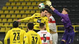 Kiper Stuttgart, Gregory Kobel, duel udara dengan bek Borussia Dortmund, Mats Hummels, pada laga Bundesliga di Stadion Signal Iduna Park, Minggu (13/12/2020). Stuttgart menang dengan skor 5-1. (AFP/Ina Fassbender)
