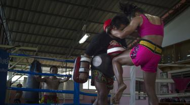 Petinju Muay Thai Nong Rose melakukan serangan dengan lututnya saat berlatih di provinsi Chachoengsao, Thailand (15/12). Bersama saudara laki-lakinya, petinju Muay Thai transgender ini melakukan sesi latihan. (AFP Photo)