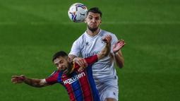 Bek Barcelona, Jordi Alba (kiri) berduel udara dengan striker SD Huesca, Rafa Mir dalam laga lanjutan Liga Spanyol 2020/2021 pekan ke-27 di Camp Nou Stadium, Barcelona, Senin (15/3/2021). Barcelona menang 4-1 atas SD Huesca. (AP/Joan Monfort)