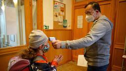 Seorang staf memeriksa suhu tubuh seorang anak perempuan di sebuah sekolah di Praha, Republik Ceko (25/5/2020). Para siswa sekolah dasar juga diizinkan untuk kembali bersekolah dalam kelompok-kelompok kecil. (Xinhua/Dana Kesnerova)
