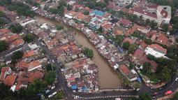 Foto udara suasana Sungai Ciliwung yang diapit pemukiman padat penduduk di kawasan Manggarai, Jakarta, Selasa (7/1/2020). Pemprov DKI Jakarta menyiapkan anggaran Rp 600 miliar untuk pembebasan 118 bidang lahan proyek normalisasi Sungai Ciliwung pada tahun 2020.(Liputan6.com/Immanuel Antonius)