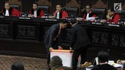 Petugas membawa kontainer berisi barang bukti milik BPN Prabowo-Sandiaga yang dihadirkan dalam sidang lanjutan sengketa Pilpres 2019 di MK, Jakarta, Rabu (19/6/2019). Sidang kali ini beragendakan mendengar keterangan saksi dan ahli terkait sengketa Pilpres 2019. (merdeka.com/Iqbal Nugroho)