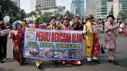 Paguyuban Seniman Badut Indonesia (PASBI) menggelar aksi Peduli Bencana Alam untuk Sulawesi Tengah di area car free day (CFD), Jakarta, Minggu (14/10). Mereka menggalang dana untuk disalurkan kepada korban bencana Sulteng. (Merdeka.com/Iqbal Nugroho)