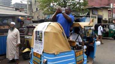Musisi jazz AS, Wycliffe Gordon memainkan terompet dalam pertunjukan jalanan di ibukota Sri Lanka, Kolombo (26/2). Wycliffe mengadakan serangkaian pertunjukan dan kelas di kota Sri Lanka di Kolombo, Matara dan Galle. (AFP Photo/Ishara S. Kodikara)