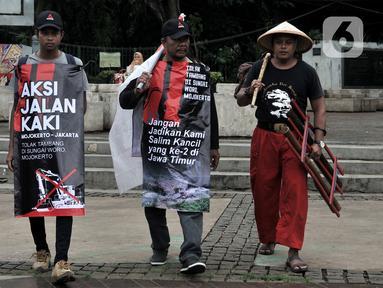 Tiga warga Mojokerto, Ahmad Yani (45), Sugiantoro (31), dan Heru Prasetiyo (24) bersama aktivis saat tiba di seberang Istana Negara, Jakarta, Kamis (6/2/2020). Mereka berjalan kaki dari Mojokerto meminta pemerintah menghentikan aktivitas penambangan di Sungai Woro. (merdeka.com/Iqbal S Nugroho)