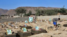 Sejumlah anak Yaman mengunjungi makam anak-anak sekolah di sebuah pemakaman di provinsi kubu pemberontak Huthi di Saada (4/9). Anak-anak tersebut tewas terkena serangan udara koalisi pimpinan Saudi saat berada di sebuah bus. (AFP Photo/Stringer)