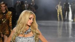 Paris Hilton berpose di atas catwalk saat mengenakan koleksi terbaru dari The Blonds dalam New York Fashion Week, AS (12/2). Paris Hilton tampil seksi mengenakan busana serba silver di atas catwalk. (AFP Photo/Mike Coppola)