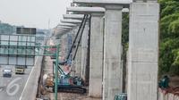 Pekerja menggunakan alat berat untuk menyelesaikan proyek kereta api ringan atau light rail transit (LRT) Jabodetabek, Bekasi, Sabtu (25/2). (Liputan6.com/Gempur M. Surya)