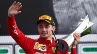 Pembalap Ferrari Charles Leclerc memegang piala sambil melambaikan tangan usai memenangkan F1 GP Italia 2019 di Sirkuit Monza, Minggu (8/9/2019). Leclerc menjuarai F1 GP Italia 2019 setelah pertarungan alot melawan duo pembalap Mercedes, Lewis Hamilton dan Valtteri Bottas. (AP Photo/Antonio Calanni)