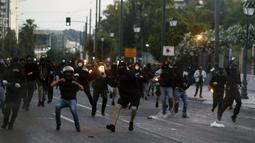 Demonstran melemparkan bom molotov ke arah polisi saat berunjuk rasa atas kematian George Floyd di luar Kedubes AS di Athena, Yunani, Rabu (3/6/2020). Kematian pria kulit hitam George Floyd saat ditangkap oleh polisi Amerika Serikat memicu kemarahan di sejumlah negara. (AP Photo/ Lefteris Pitarakis)