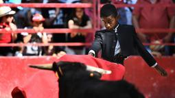 Seorang anak bernama Kilian (10) bertarung melawan banteng kecil saat belajar menjadi matador di arena adu banteng Franquevaux di sekolah adu banteng, Prancis selatan (20/5). (AFP Photo/Anne-Christine Poujoulat)