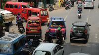 Sebuah angkutan umum menurunkan penumpang di tengah jalan dekat pertigaan Stasiun Lenteng Agung, Jakarta, Rabu (2/12/2015). Kurangnya kesadaran warga menaati peraturan lalu lintas seringkali berimbas pada kemacetan. (Liputan6.com/Helmi Fithriansyah)