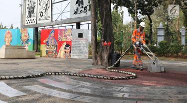 Petugas menggunakan alat ThruKlin untuk membersihkan beton berpori di area Taman Pandang Istana, Jakarta, Kamis (2/8). Alat pembersih ThruCrete atau beton berpori ini diujicoba penggunaannya. (Liputan6.com/Helmi Fithriansyah)