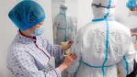 Petugas medis Rumah Sakit Afiliasi Universitas Qingdao memeriksa baju pelindung rekannya di Rumah Sakit Tongji cabang Guanggu di Wuhan, 20 Februari 2020. Beberapa langkah pencegahan dilakukan secara ketat selama dan sesudah jam kerja oleh pekerja medis untuk melawan virus corona. (Xinhua/Cai Yang)