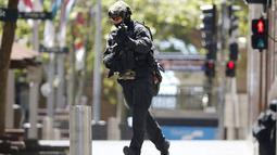 Seorang polisi berlari mengepung situasi kafe Lindt di Sydney, Australia (15/12/2014). Puluhan sandera terperangkap di dalam kafe Lindt di Sydney, Australia. (REUTERS/Jason Reed)