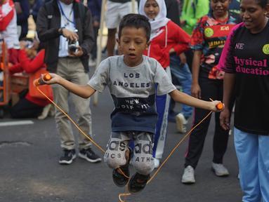 Seorang anak mencoba olahraga lompat tali atau jumping rope bersama komunitas penggerak olahraga di tengah kegiatan Car Free Day kawasan Bundaran Hotel Indonesia, Minggu (30/6/2019). Kegiatan tersebut mengajak masyarakat untuk hidup sehat dengan berolahraga. (Liputan6.com/Immanuel Antonius)